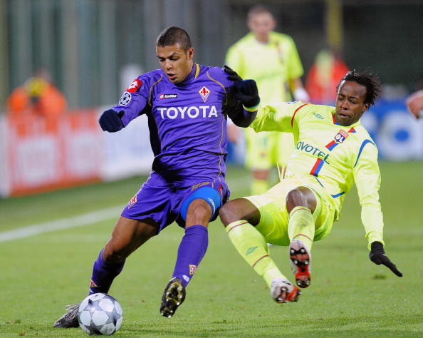Lyon's forward Sidney Govou (R) tackles