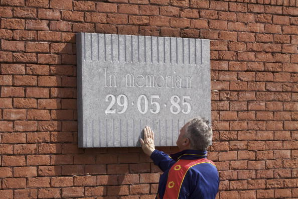 A man presses his hand against a plaque